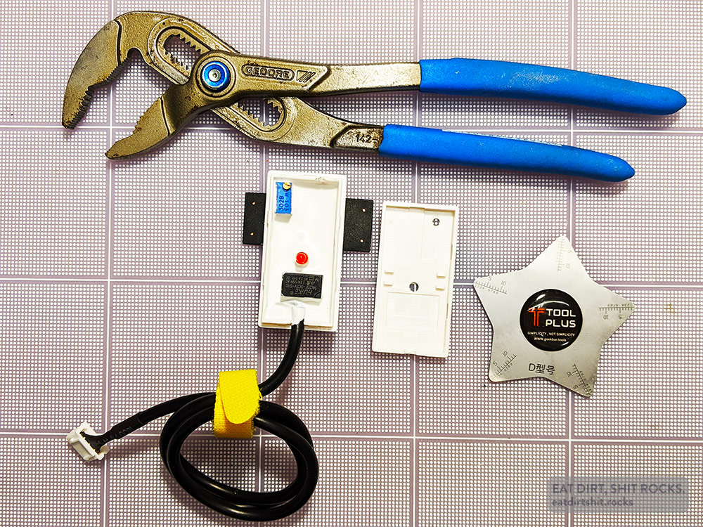 Shot showing one sensor with its cover removed, along with the tools I used to pry it open.